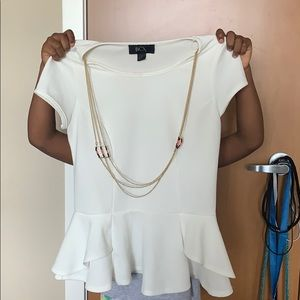 A white blouse with an attached gold necklace.